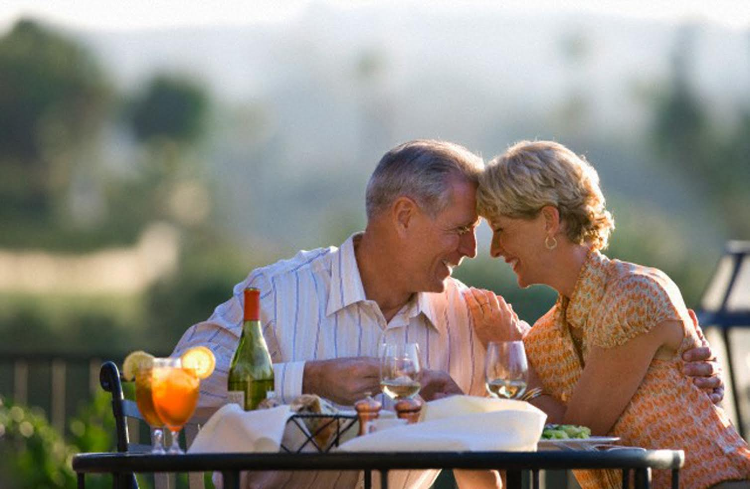 Mature couple dining at outdoor restaurant table, leaning affectionately forehead to forehead, smiling, profile --- Image by © Juice Images/Corbis